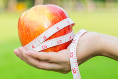 Woman hand holding fresh apple with measuring tape Stock Photos