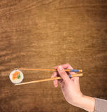 Woman hand holding fresh maki sushi roll Stock Photography