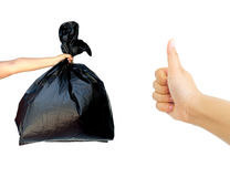 Woman hand holding garbage bag with hand showing thumb up isolated Stock Photography