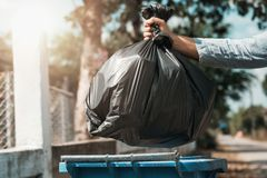 Woman hand holding garbage bag put in to trash. Woman hand holding garbage black bag put in to trash royalty free stock photography