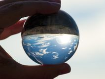 Woman hand holding glass ball with panoramic view of countryside and sky/ Concept for environment. Woman hand holding glass ball with panoramic view of stock images