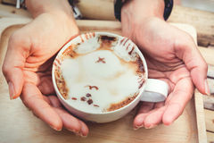Woman hand holding a glass of hot latte Ars. Stock Image