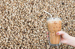 Woman hand holding the glass iced coffee on unroasted coffee raw beans background Stock Photography