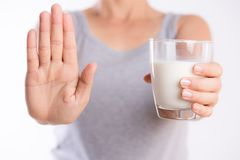 Woman hand holding glass of milk having bad stomach ache because of Lactose intolerance and another hand shows stop sign. health. Problem with dairy food royalty free stock images