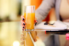 Woman hand holding glass of orange juice Royalty Free Stock Image