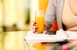 Woman hand holding glass of orange juice Royalty Free Stock Photos