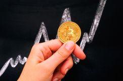 Woman hand holding golden Bitcoin virtual coin against blackboar. D with chalk drawing graph Royalty Free Stock Photo
