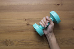 Woman hand holding green dumbbell on wood table background Stock Image