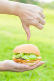 Woman hand holding hamburger and dislike fast food Stock Images