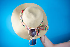 Woman hand holding hat and sunglasses against blue Royalty Free Stock Photography