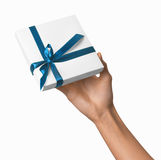 Woman Hand holding Holiday Present White Box with Blue Ribbon Stock Images
