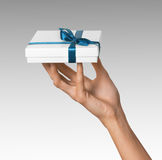 Woman Hand holding Holiday Present White Box with Blue Ribbon Royalty Free Stock Photos