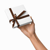 Woman Hand holding Holiday Present White Box with Brown Ribbon Royalty Free Stock Photos