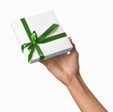 Woman Hand holding Holiday Present White Box with Green Ribbon Royalty Free Stock Photography