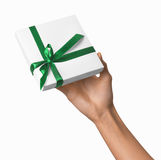 Woman Hand holding Holiday Present White Box with Green Ribbon Royalty Free Stock Image