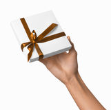 Woman Hand holding Holiday Present White Box with Orange Golden Ribbon Royalty Free Stock Photos