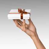 Woman Hand holding Holiday Present White Box with Orange Golden Ribbon. Woman Hand holding Present White Box with Orange Golden Ribbon Royalty Free Stock Image