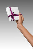 Woman Hand holding Holiday Present White Box with Pink Ribbon Royalty Free Stock Images