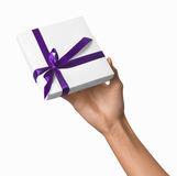 Woman Hand holding Holiday Present White Box with Purple Ribbon Royalty Free Stock Photography