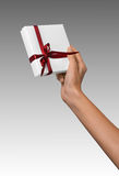 Woman Hand holding Holiday Present White Box with Red Ribbon. Woman Hand holding Present White Box with Red Ribbon Stock Images