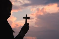 Woman hand holding holy lift of christian cross with light sunset background. Silhouette of woman hand holding holy lift of christian cross with light sunset stock photo