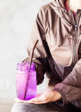 Woman hand holding iced drink in violet glass Stock Photos