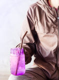 Woman hand holding iced drink in violet glass Royalty Free Stock Photography