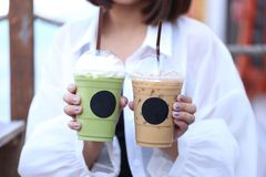 Woman hand holding Iced matcha green tea and cold coffee for summer drink royalty free stock image