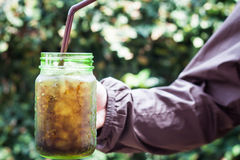 Woman hand holding iced soda in green glass Stock Photography