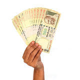 Woman hand holding Indian five hundred rupee notes. Against white background stock photos