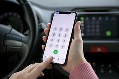 Woman hand holding iPhone X with call number in car Royalty Free Stock Photos