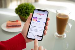 Woman hand holding iPhone X with social networking service Insta royalty free stock image