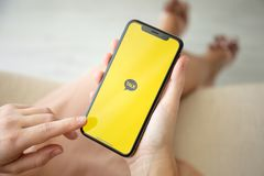 Woman hand holding iPhone X with social networking service KakaoTalk. Alushta, Russia - July 29, 2018: Woman hand holding iPhone X with social networking service royalty free stock image