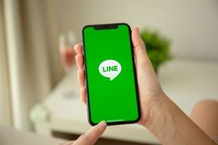 Woman hand holding iPhone X with social networking service Line. Alushta, Russia - July 29, 2018: Woman hand holding iPhone X with social networking service Line stock image
