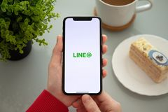Woman hand holding iPhone X with social networking service Line stock image