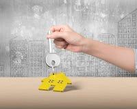 Woman hand holding key with house shape keyring, 3D illustration Stock Photo