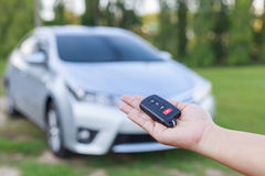 Woman hand holding key of new car Stock Photos