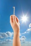 Woman hand holding key. Hand holding key on sunny sky background Stock Photography