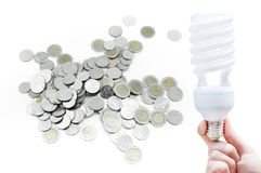 Woman hand holding light bulb on Coin on white background stock image