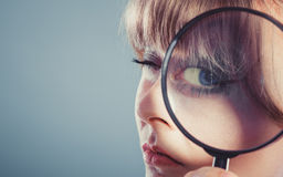 Woman hand holding magnifying glass on eye Stock Images