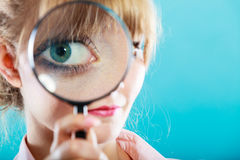 Woman hand holding magnifying glass on eye Royalty Free Stock Images