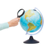 Woman hand holding magnifying glass over globe Royalty Free Stock Photography