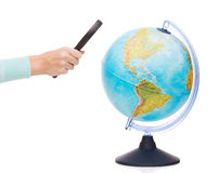 Woman hand holding magnifying glass over globe Stock Image