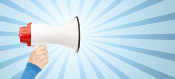 Woman hand holding megaphone over blue burst rays. Business, people and public announcement concept - close up of female hand holding megaphone over blue burst Stock Photo