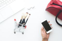 Woman hand holding mobile device with shopping cart and cosmetic items and laptop on white background, Top view online shopping Stock Image