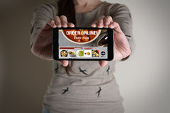 Woman hand holding mobile with order food online. Delivery service concept royalty free stock photos