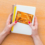 Woman hand holding notebook and credit card Royalty Free Stock Photos