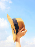 Woman hand holding panama hat with sky Stock Images