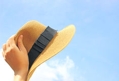 Woman hand holding panama hat with sky Royalty Free Stock Photos