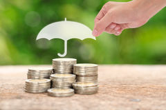 Woman hand holding a paper umbrella stacks and heaps of coins,. Nature background. Coverage, insurance or protection concept Royalty Free Stock Photo